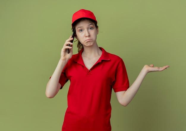 Смущенная молодая симпатичная доставщица в красной форме и кепке разговаривает по телефону и показывает пустую руку, изолированную на оливково-зеленом фоне с копией пространства