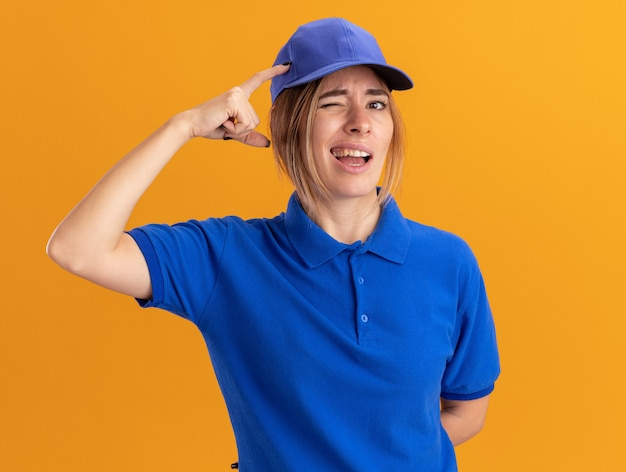 Confused young pretty delivery girl in uniform puts finger on head and looks at camera on orange