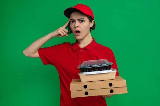 ピザの箱に食品容器とパッケージを保持している混乱した若いかわいい配達の女性