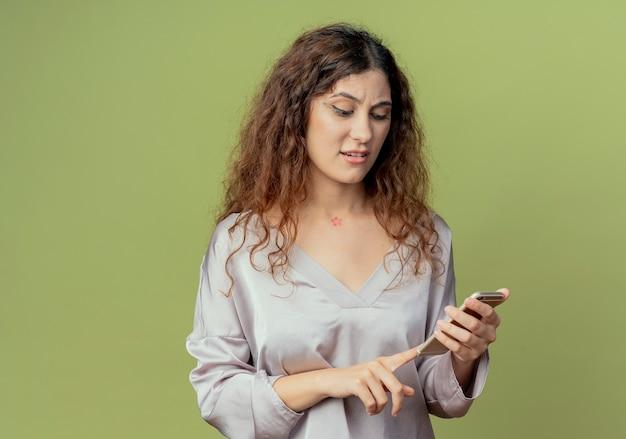 Смущенный молодой симпатичный женский офисный работник набирает номер на телефоне, изолированном на оливково-зеленой стене