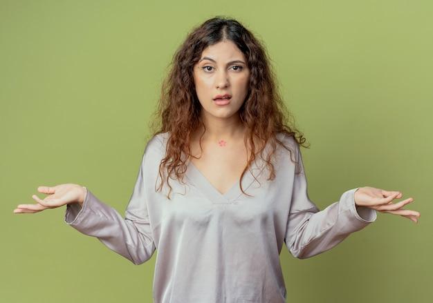 혼란 스 러 워 젊은 예쁜 여성 회사원 올리브 녹색 벽에 고립 된 손을 확산
