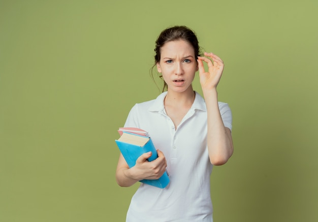 Confused young pretty female student holding book and note pad keeping hand in air pretend holding something isolated on olive green background with copy space