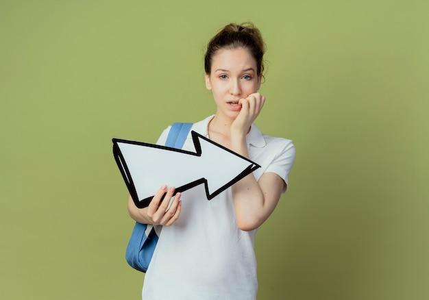 Смущенная молодая симпатичная студентка в сумке на спине, держащая стрелку, которая указывает на сторону и кладет руку на губу, изолированную на оливково-зеленом фоне с копией пространства
