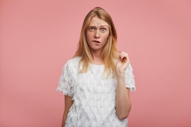 Confusa giovane donna graziosa con capelli volpi che aggrotta le sopracciglia e morde il labbro inferiore mentre si trova su sfondo rosa con la mano alzata, vestito con abiti eleganti
