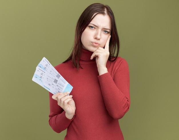 コピースペースでオリーブグリーンの壁に隔離された顔に手を置いて飛行機のチケットを保持している混乱した若いかわいい女の子