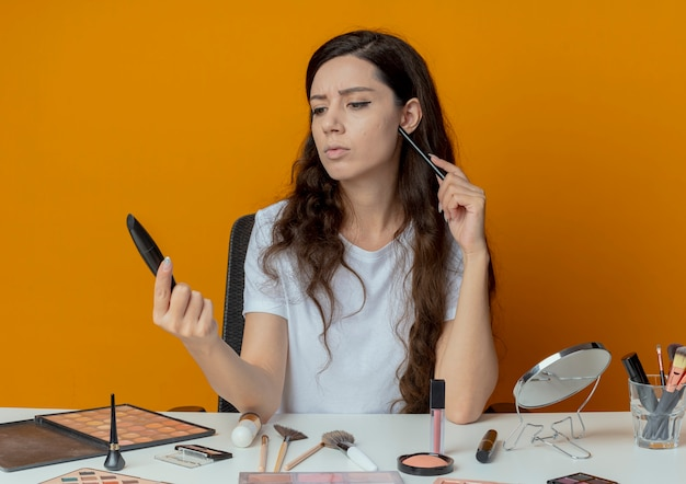 Смущенная молодая красивая девушка, сидящая за макияжным столом с инструментами для макияжа, держащая подводку для глаз и тушь, смотрит на тушь и трогает лицо подводкой для глаз, изолированной на оранжевом фоне