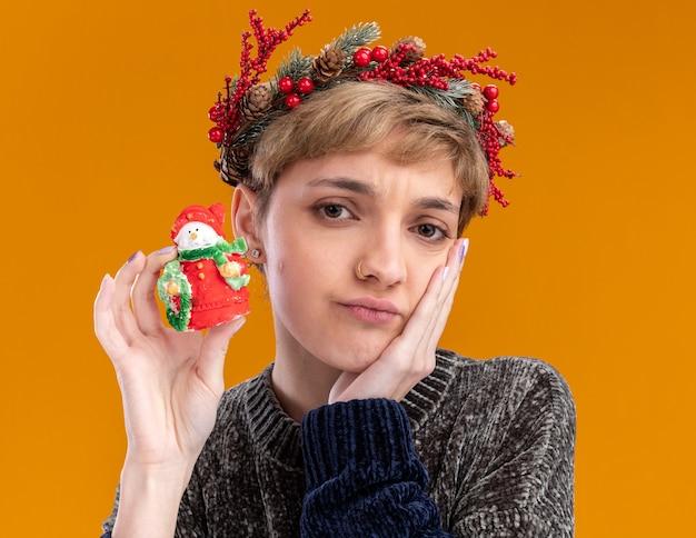 Giovane ragazza graziosa confusa che indossa la corona della testa di natale che tiene la piccola statua del pupazzo di neve di natale che tiene la mano sul fronte che guarda l'obbiettivo isolato su fondo arancio