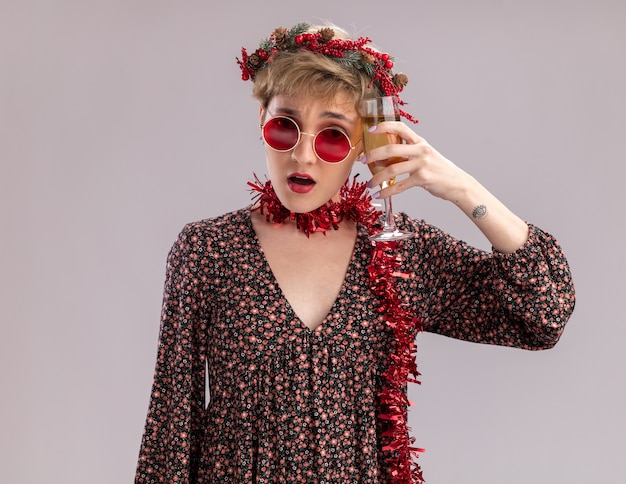 Confused young pretty girl wearing christmas head wreath and tinsel garland around neck with glasses touching head with glass of champagne looking at camera isolated on white background