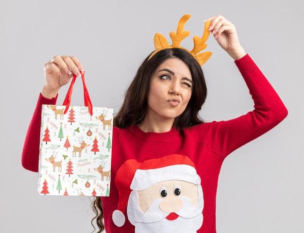 トナカイの角のヘッドバンドとサンタクロースのセーターを身に着けている混乱した若いかわいい女の子は、白い壁に隔離された片目を閉じて横を見てヘッドバンドをつかむクリスマスギフトバッグを保持しています