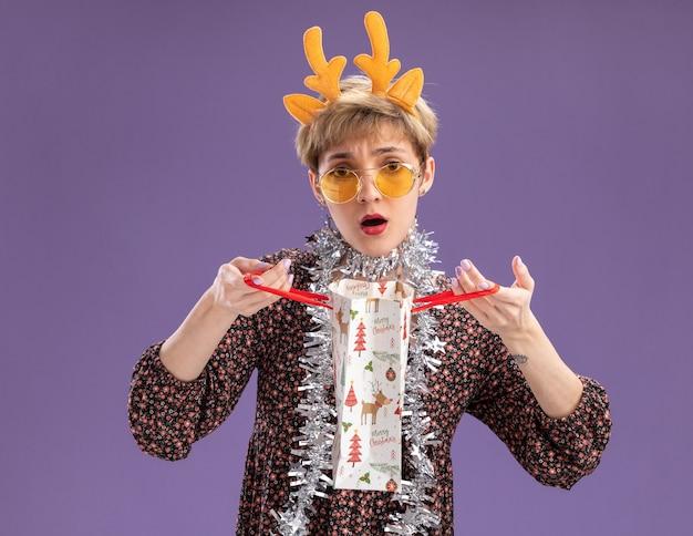 Confusa giovane bella ragazza che indossa la fascia di corna di renna e la ghirlanda di orpelli intorno al collo con gli occhiali che tengono il sacchetto del regalo di natale che guarda l'obbiettivo isolato su priorità bassa viola