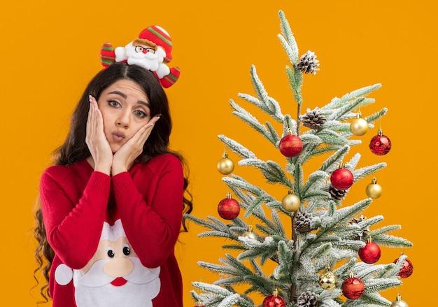 サンタクロースのヘッドバンドとセーターを着て、オレンジ色の背景に分離されたカメラの財布の唇を見て顔に手を置いて飾られたクリスマスツリーの近くに立っている混乱した若いかわいい女の子