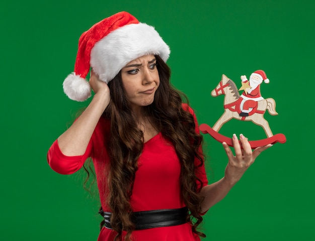 Confused young pretty girl wearing santa hat holding santa on rocking horse figurine looking at it keeping hand on head isolated on green background