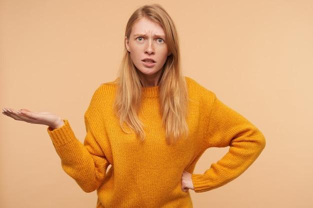 Confuso giovane donna graziosa rossa aggrottando le sopracciglia e sollevando perplesso il palmo mentre si trovava sul beige in maglia senape pullon