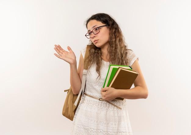 Scolara giovane graziosa confusa con gli occhiali e borsa posteriore che tiene i libri che mostrano la mano vuota che esamina il lato isolato su bianco con lo spazio della copia