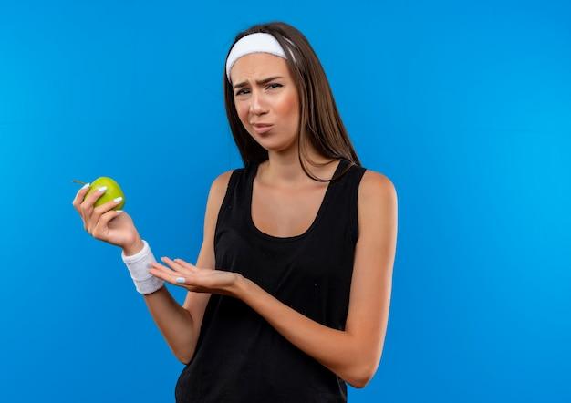 Смущенная молодая симпатичная спортивная девушка с головной повязкой и браслетом, держащая и указывающая на яблоко, изолированное на синей стене с копией пространства