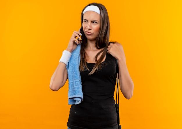 Смущенная молодая симпатичная спортивная девушка с повязкой на голову и браслетом разговаривает по телефону, глядя в сторону с полотенцем и прыгает через скакалку на плечах, изолированную на оранжевой стене