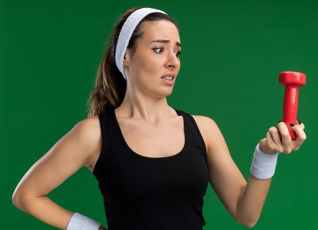 머리띠와 팔찌를 착용하고 허리에 손을 대고 녹색 벽에 격리된 덤벨을 보고 있는 혼란스러운 젊고 스포티한 소녀