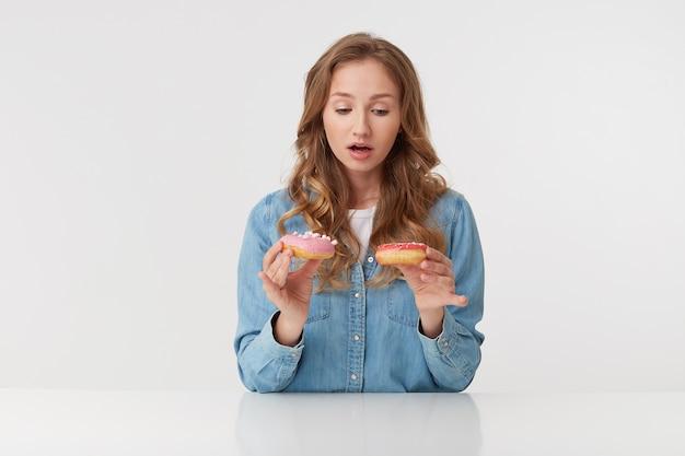 Смущенная молодая симпатичная женщина с длинными светлыми волнистыми волосами в джинсовой рубашке не может решить, какой из двух пончиков выбрать.