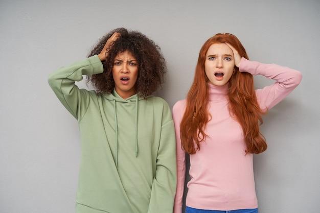 Giovani belle donne confuse che tengono la mano alzata sulle loro teste mentre stanno sopra il muro grigio, aggrottano le sopracciglia e tengono la bocca aperta mentre guardano