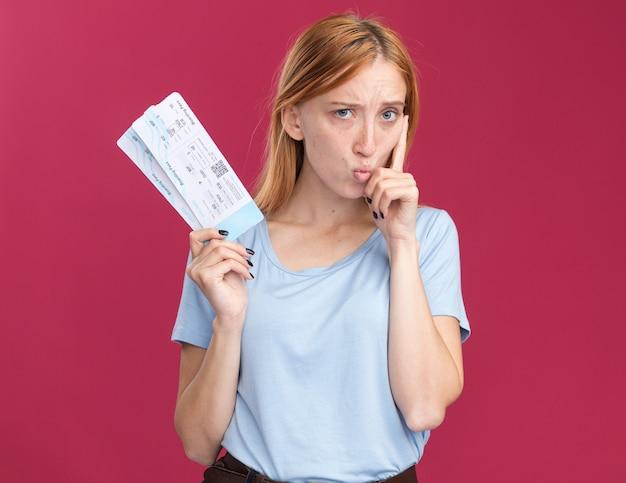 航空券を保持しているそばかすと混乱した若い赤毛生姜の女の子