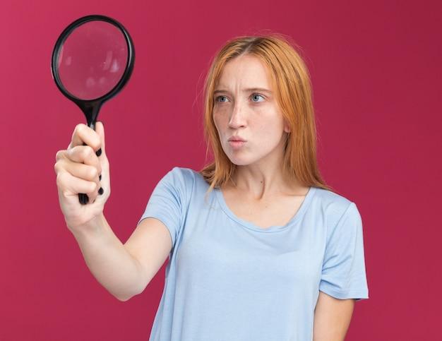 ピンクの虫眼鏡を持って見ているそばかすと混乱した若い赤毛生姜の女の子