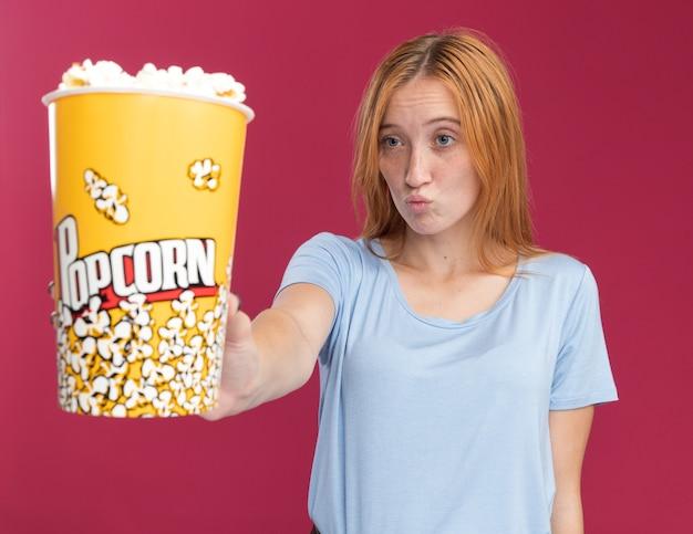 Ragazza confusa dello zenzero giovane rossa con le lentiggini tenendo e guardando il secchio di popcorn sul rosa