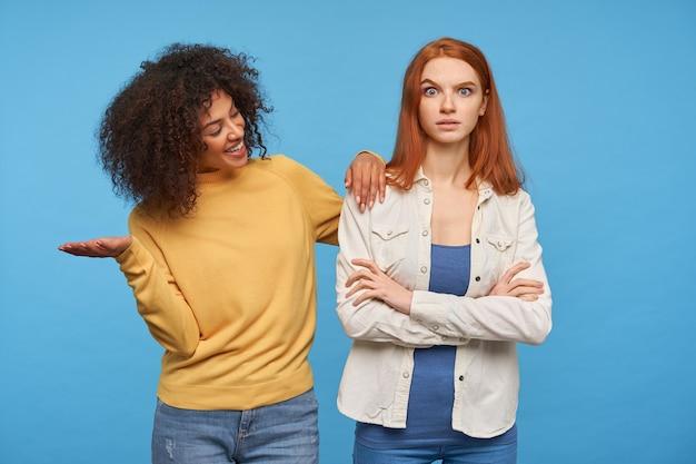 Смущенная молодая рыжая дама удивленно приподняла бровь и сложила руки на груди, пока позирует со своей довольно веселой кудрявой темнокожей подругой-брюнеткой над синей стеной
