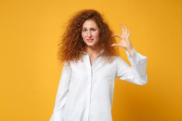 노란색 오렌지 벽에 고립 된 캐주얼 흰색 셔츠 포즈에 혼란 스 러 워 젊은 빨간 머리 여자 소녀