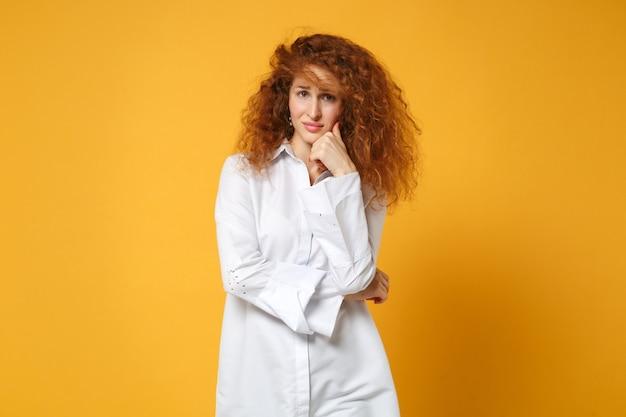 Смущенная молодая рыжая девушка в повседневной белой рубашке позирует изолированной на желто-оранжевой стене