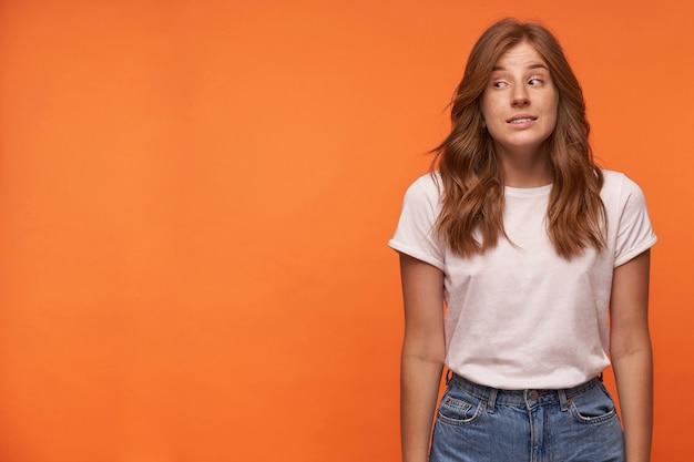 Confusa giovane donna rossa che indossa jeans blu e t-shirt bianca. guardando da parte e contraendo la fronte, isolata