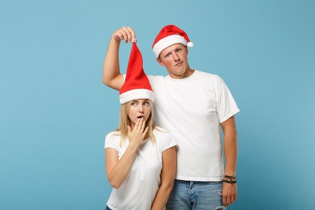クリスマスの帽子のポーズで混乱した若いサンタカップルの友人の男と女