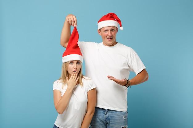 Confuso giovane santa coppia amici ragazzo e donna in cappello di natale in posa