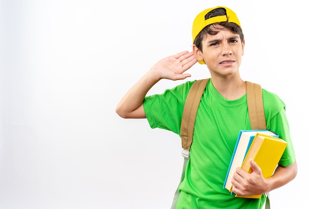Confused young school boy wearing backpack with cap holding books showing listen gesture