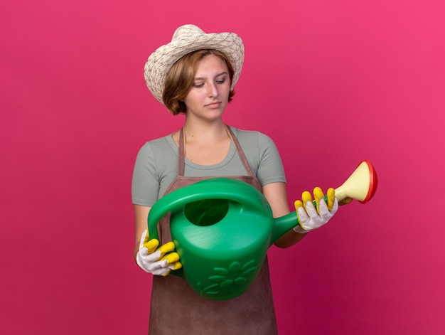 Confused young slavic female gardener wearing gardening hat and gloves holding and looking at watering can