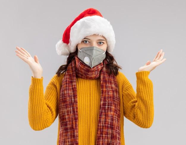 サンタの帽子と首の周りのスカーフと医療マスクを身に着けている混乱した若いスラブの女の子は、コピースペースで白い壁に隔離された手を開いて