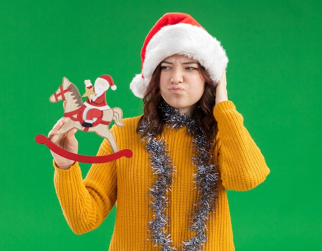 Confused young slavic girl with santa hat and with garland around neck holding and looking at santa on rocking horse decoration isolated on green wall with copy space