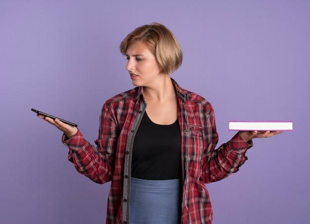 La giovane studentessa slava confusa tiene il telefono e il libro