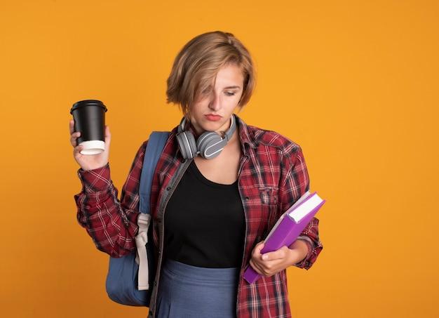 배낭을 착용하는 헤드폰으로 혼란 스 러 워 젊은 슬라브 학생 소녀 종이 컵을 보유하고 책과 노트북을 본다