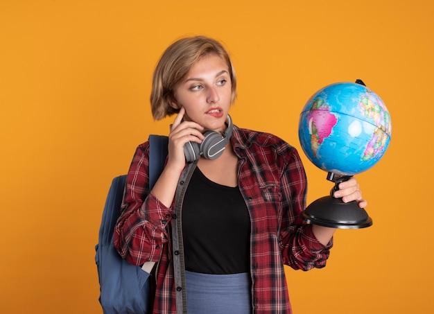 バックパックを着たヘッドフォンで混乱した若いスラブ学生の女の子が顔に指を置き、地球儀を持って見ている