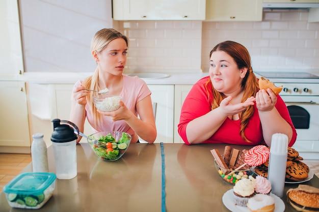 混乱している若いスリムなモデルは、テーブルでファーマーチーズを食べます。彼女はハンバーガーとジャンクフードを食べるプラスサイズのモデルを見てください。ハッピーボディ正。健康で不健康なライフスタイル。