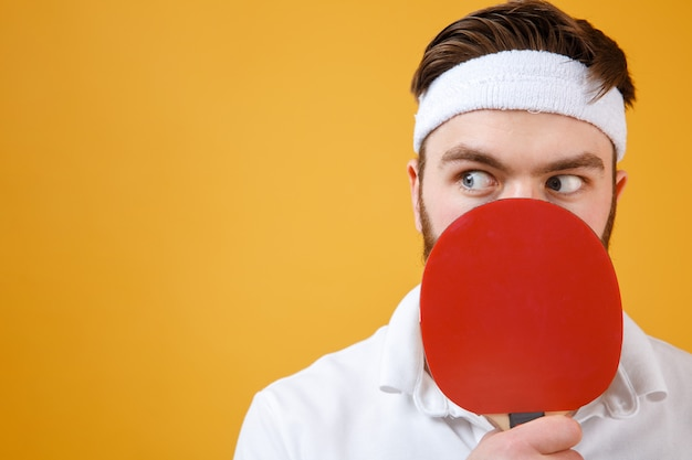 Confused young sportsman holding racket for table tennis covering mouth