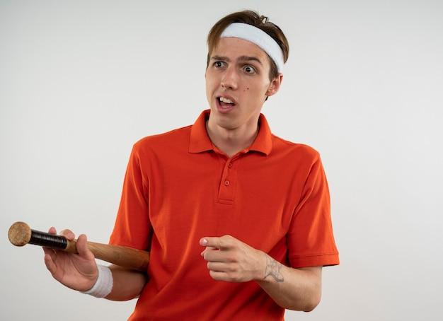 측면에서 야구 방망이 포인트를 들고 팔찌와 머리띠를 착용하는 측면을보고 혼란 스 러 워 젊은 스포티 한 남자