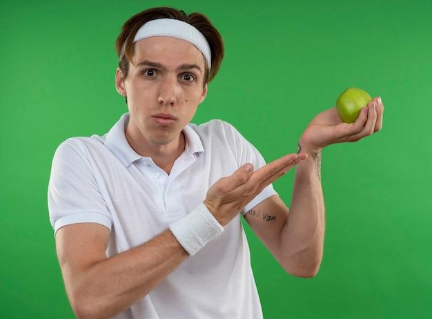 Смущенный молодой спортивный парень в головной повязке с браслетом и указывает рукой на яблоко