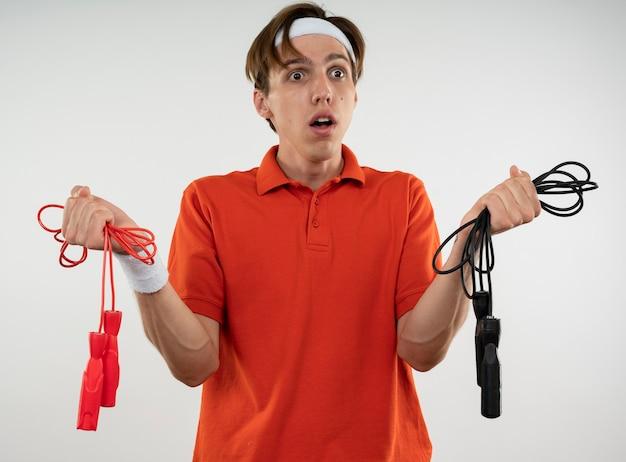 Confuso giovane ragazzo sportivo che indossa la fascia con il braccialetto che tiene le corde per saltare isolate su bianco