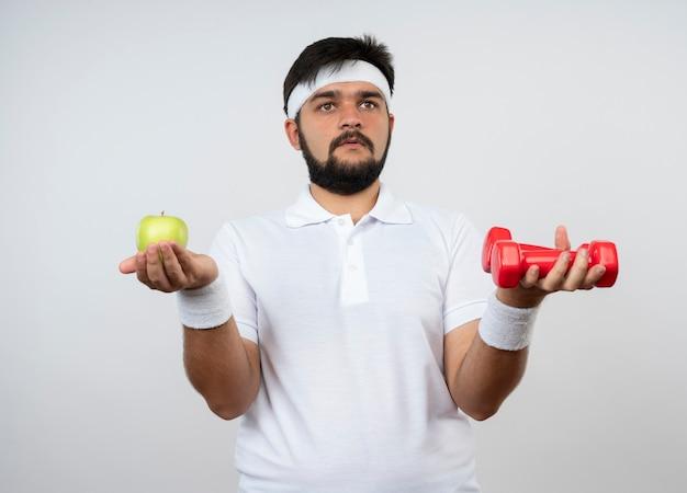Смущенный молодой спортивный человек, смотрящий на боковую повязку на голову и браслет, держащий гантели с яблоком на белой стене