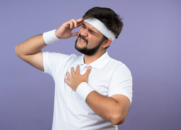 Смущенный молодой спортивный человек с повязкой на голову и браслет, положив руку на храм, изолированный на зеленой стене