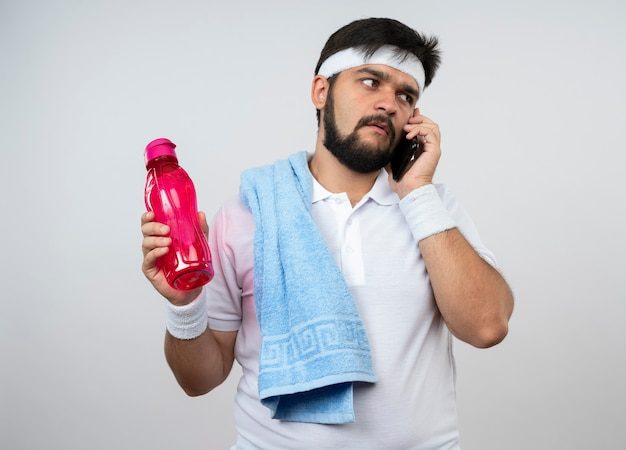 물병을 들고 어깨에 수건으로 머리띠와 팔찌를 착용하는 혼란 스 러 워 젊은 스포티 한 남자가 흰 벽에 고립 된 전화에 말한다