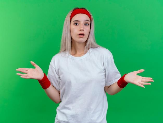 Confusa giovane donna sportiva con bretelle che indossa la fascia e braccialetti tiene le mani aperte isolate sulla parete verde
