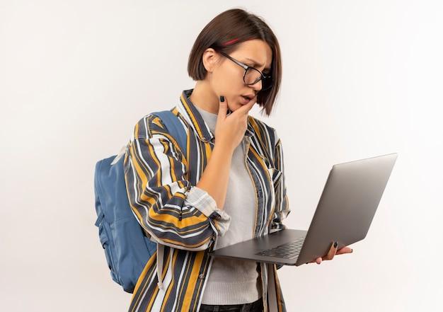 Смущенная молодая студентка в очках и задней сумке, держащая и смотрящую на ноутбук с рукой на подбородке, изолированной на белом