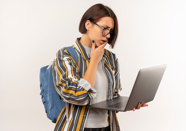 Ragazza giovane studente confuso con gli occhiali e borsa posteriore che tiene e guardando il computer portatile con la mano sul mento isolato su bianco